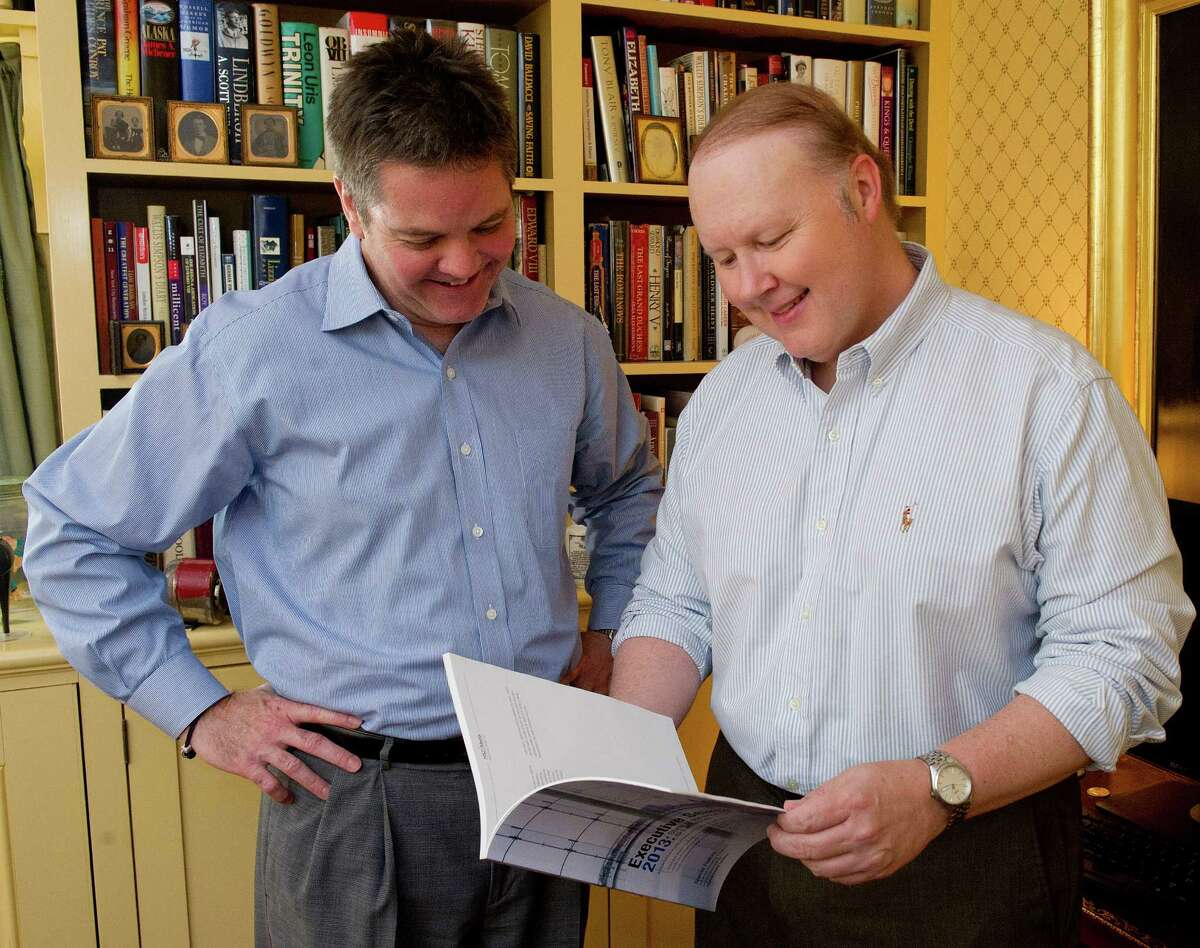 Scott Scanlon, left, and Christopher Hunt, right, of HSZ Media pose for a photo with their 2013 Executive Search State of the Industry Report on Thursday, May 29, 2014. This year's version of the report came out this month.