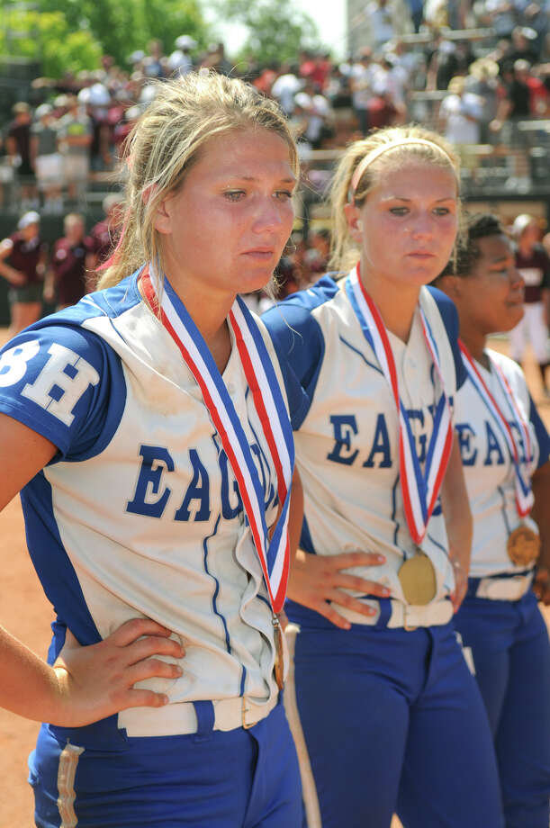 Barbers Hill senior pitcher Randi Rupp, from left, her twin sister Sara, the Eagle's catcher, and their teammates stand after receiving their medals after losing to Ennis 8-7 in their Class 4A semifinal matchup at the 2014 UIL Softball State Championsips at McCombs Field in Austin on Friday. Photo: Jerry Baker, For The Chronicle