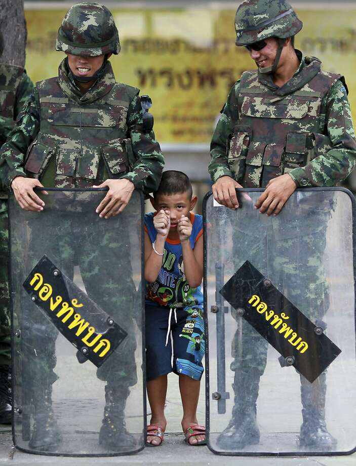 Thai fighter:A young enlistee joins Thai soldiers keeping order near the Victory Monument in Bangkok. An anti-coup activist called for a weekend rally to defy the new junta's ban on demonstrations, urging those opposed to the takeover to wear masks. Photo: Wason Wanichakorn, Associated Press
