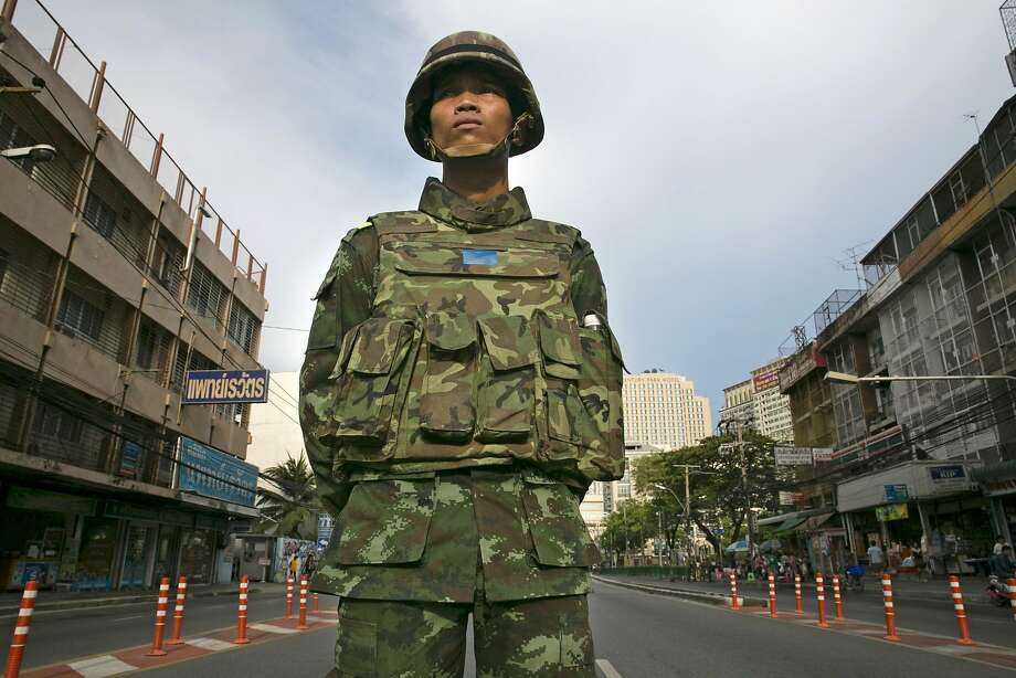 A soldier guards a Bangkok street closed to traffic to stop anticoup protesters from gathering. Photo: Paula Bronstein, Getty Images