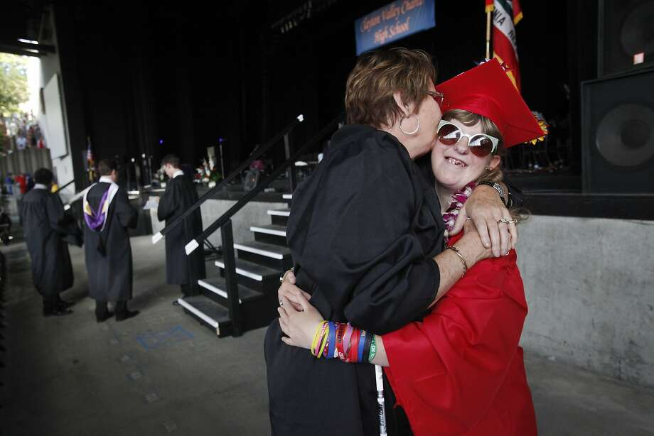 Katie Westbrook (right), who has a rare genetic condition, is hugged by Janet Holstad before her graduation. Photo: Leah Millis, The Chronicle