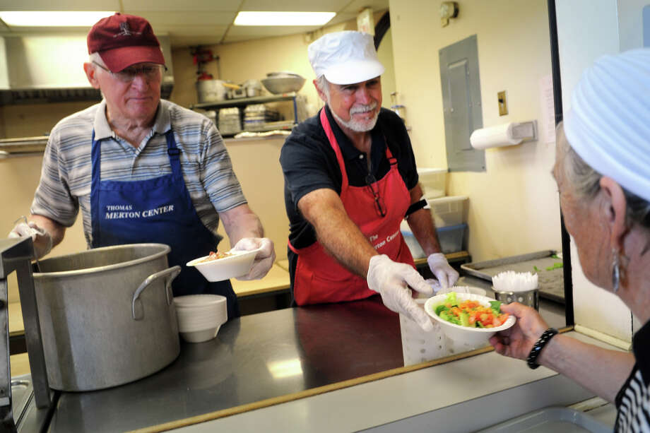 Volunteers Joe Sommers, left, and Jorge Shopis serves lunch to clients at The Thomas Merton House of Hospitality, part of The Thomas Merton Center, in Bridgeport, Conn. May 27, 2014. Photo: Ned Gerard / Connecticut Post