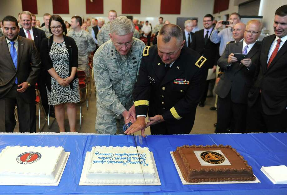 Major Gen. Thaddeus J. Martin, left, and Brigadier Gen. Dwayne R. Edwards cut a commemorative cake with a sword at the Ribbon-Cutting and Memorialization Ceremony at the Veterans Memorial Armed Forces Reserve Center in Danbury, Conn. on Friday, May 30, 2014.  The Army Reserve's 99th Regional Support Command, in cooperation with the Connecticut Army National Guard, officially opened and dedicated its new $35 million facility.  The 96,000 square foot facility will be home to approximately 600 soldiers assigned to four Army Reserve and two National Guard units.  The building was named in honor of the veterans of Danbury. Photo: Tyler Sizemore / The News-Times