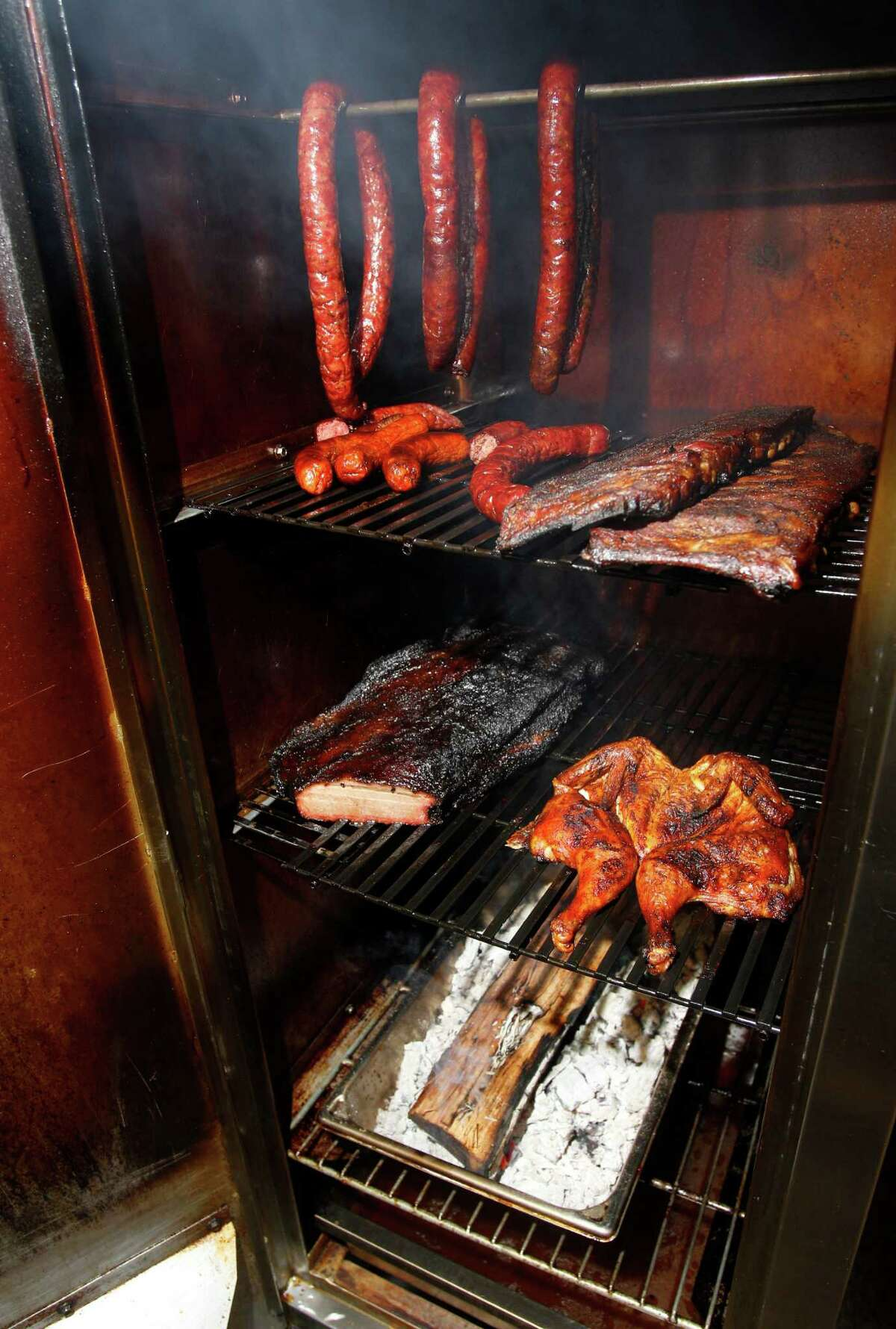Will Buckman takes meat off the smoker at Corkscrew BBQ in Spring.