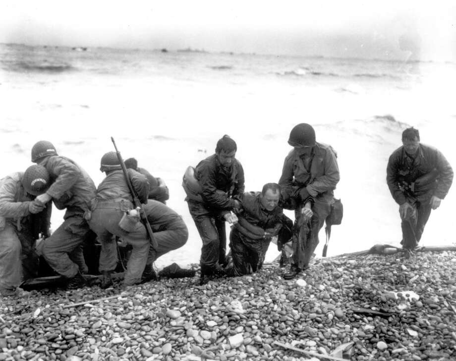 Members of an American landing unit help their exhausted comrades ashore during the Normandy invasion, in this June 6, 1944, photo. The men reached the zone code-named Utah Beach, near Sainte-Mere-Eglise, on a life raft, after their landing craft was hit and sunk by German coastal defenses. / U.S. ARMY