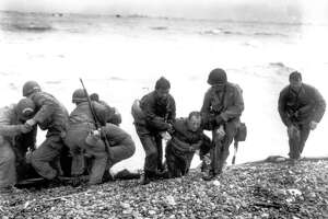 Members of an American landing unit help their exhausted comrades ashore during the Normandy invasion, in this June 6, 1944, photo. The men reached the zone code-named Utah Beach, near Sainte-Mere-Eglise, on a life raft, after their landing craft was hit and sunk by German coastal defenses.