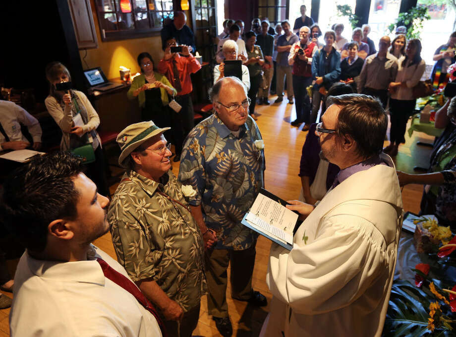 Matthew Friday (center, left) exchanges wedding vows with Bruce Carlson as United Methodist Pastor Warren Light officiates during a ceremony Eugene, Oregon. The couple have been together 28 years. Photo: Chris Pietsch / Eugene Register-Guard / The Register-Guard