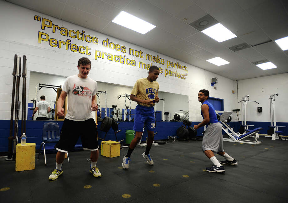 Cade Therot, Jared Thomas, and Zackary Roberts, left to right, warm up before their exercises Thursday afternoon. Monsignor Kelly Catholic High School football players exercised Thursday afternoon as they began prep for the following fall season. Photo taken Thursday 5/29/14 Jake Daniels/@JakeD_in_SETX Photo: Jake Daniels / ©2014 The Beaumont Enterprise/Jake Daniels