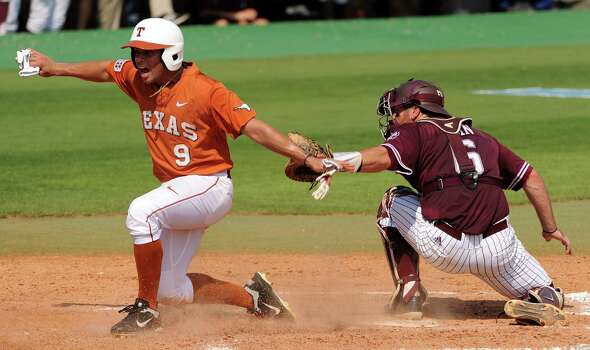 Texas' C.J. Hinojosa, left, signals himself safe after scoring a run as Texas A&M catcher Troy Stein applies a late tag during the third inning of a Houston NCAA baseball regional game, Friday, May 30, 2014, at Reckling Park in Houston. Photo: Eric Christian Smith, For The Chronicle