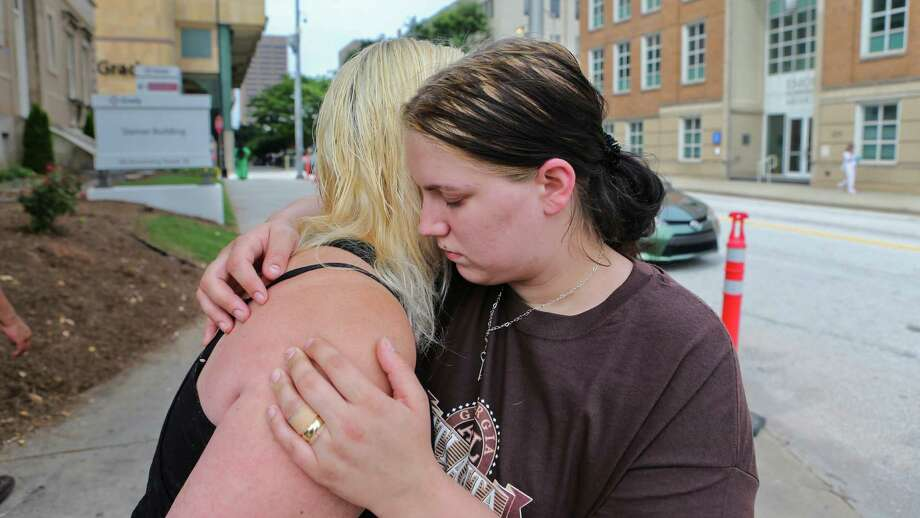 Alecia Phonesavanh, right, is hugged by her mother, Marlene Haygood, left, on Thursday, May 30, 2014 in Atlanta as they talk about  an incident in which Phonesavanh's 19-month-old boy was critically injured when a police device was tossed into his bed Wednesday morning in Habersham County by a SWAT team in search of a drug suspect. Phonesavanh said there is no way officers should not have known they were children in the house. Habersham County Sheriff Joey Terrell said the officers were looking for a suspect who may have been armed and followed proper procedure by using the device. Photo: John Spink, AP / Atlanta Journal-Constitution