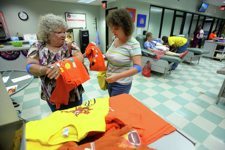 Aris Gibbins, left, and Vel Williams pick up free shirts after giving blood at Life Share in Beaumont on Monday. Life Share is using unique prizes like generators and Hurricane preparedness materials to bring in donors. Photo taken May 30, 2014 Guiseppe Barranco/@spotnewsshooter Photo: Guiseppe Barranco, Photo Editor
