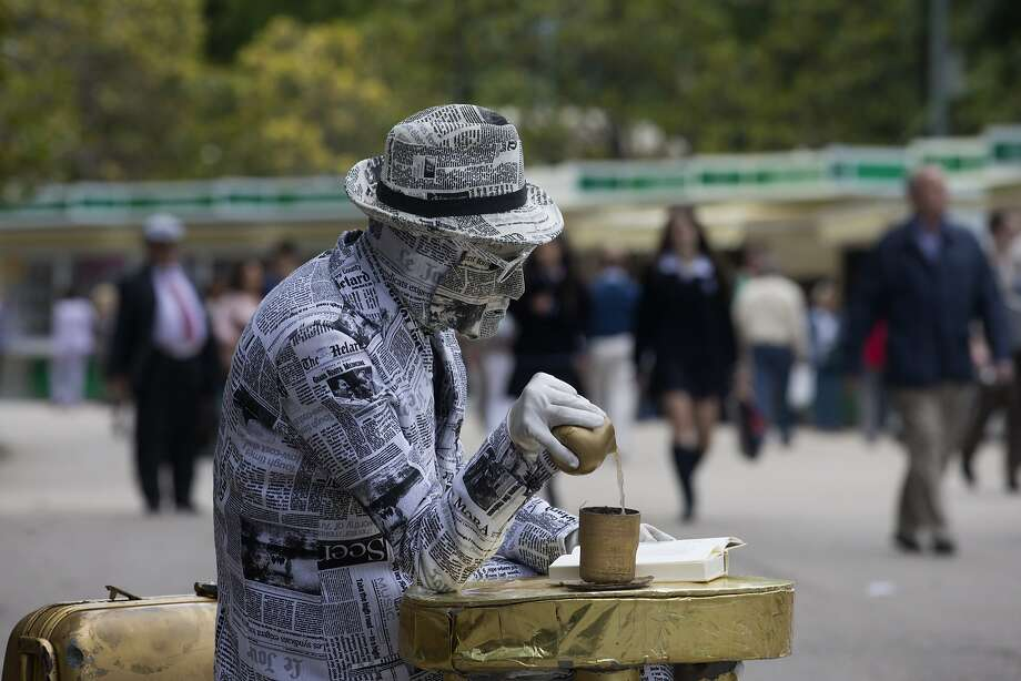 Sorry, we get all our news from the Internet now:A mime artist covered in newspapers looks for handouts at a book fair in Madrid. Photo: Paul White, Associated Press