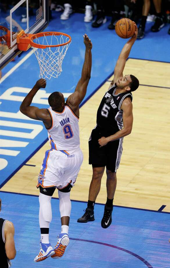 OKLAHOMA CITY, OK - MAY 27:  Cory Joseph #5 of the San Antonio Spurs goes up for a dunk against Serge Ibaka #9 of the Oklahoma City Thunder in the second half during Game Four of the Western Conference Finals of the 2014 NBA Playoffs at Chesapeake Energy Arena on May 27, 2014 in Oklahoma City, Oklahoma. NOTE TO USER: User expressly acknowledges and agrees that, by downloading and or using this photograph, User is consenting to the terms and conditions of the Getty Images License Agreement. Photo: Joe Robbins, Getty Images / 2014 Getty Images