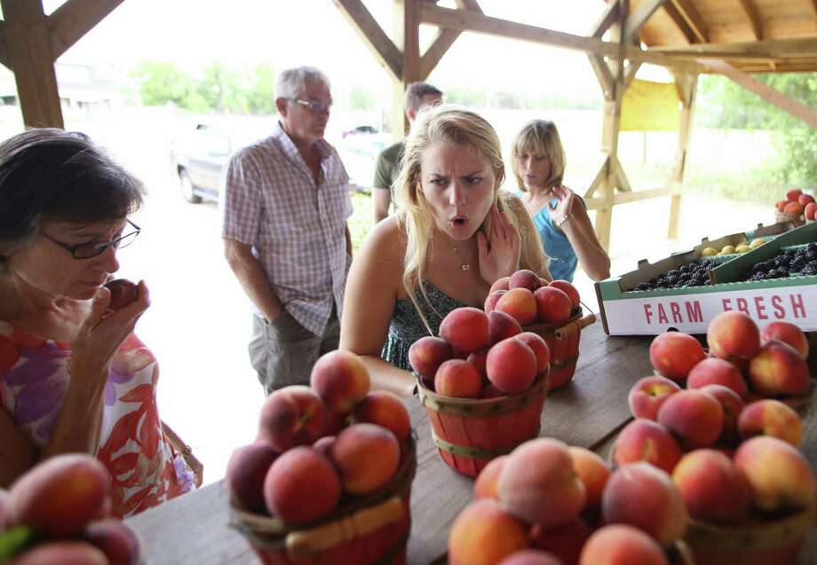 Miki Roberts, of Canyon Lake, reacts excitedly after smelling fresh peaches as her mother, Sandy Roberts (left), takes a sniff at Studebaker Farm fruit stand in Blumenthal, near Fredericksburg. Early peach varieties fill the fruit stand, which is open daily. Photo: Photos By Timothy Tai / San Antonio Express-News / © 2014 San Antonio Express-News