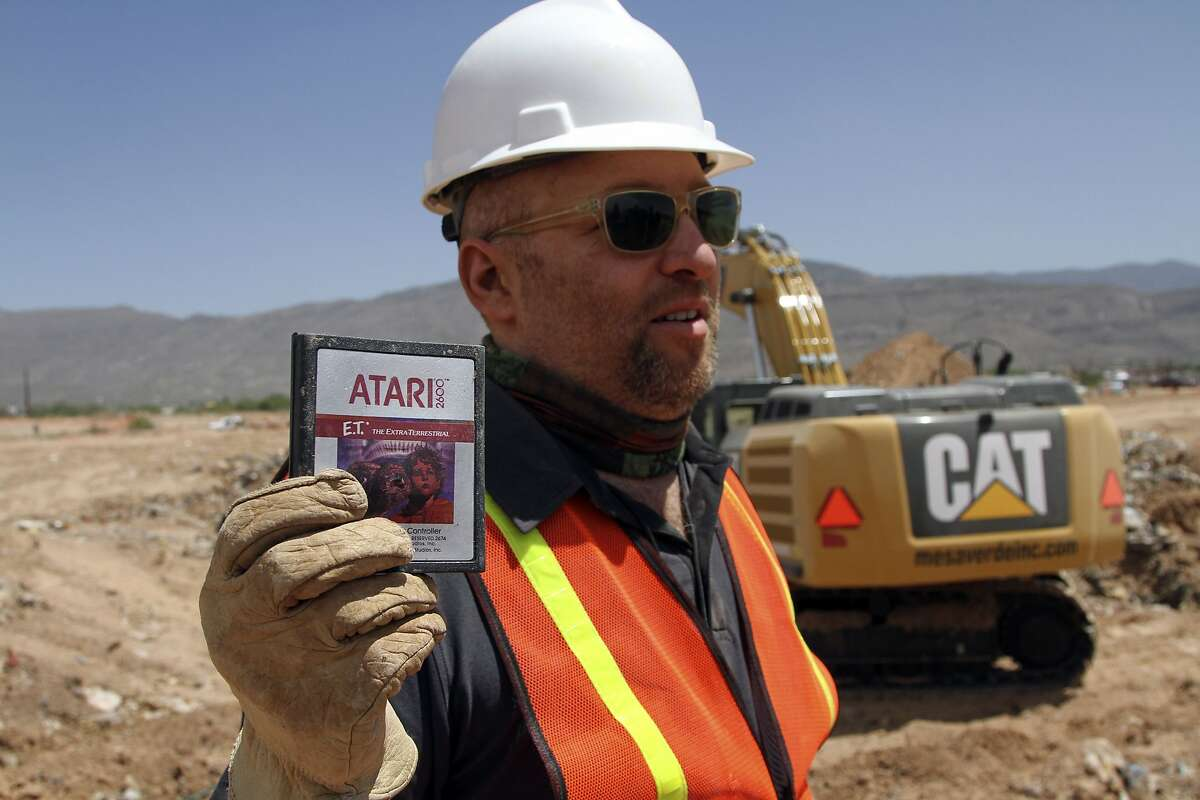 FILE - In this April 26, 2014 file photo, film Director Zak Penn shows a box of a decades-old Atari 'E.T. the Extra-Terrestrial' game found in a dumpsite in Alamogordo, N.M., Producers of a documentary dug in an southeastern New Mexico landfill in search of millions of cartridges of the Atari 'E.T. the Extra-Terrestrial' game that has been called the worst game in the history of video gaming and were buried there in 1983. Officials in Alamogordo, are working on a plan under which film companies, museums and the public could get Atari video games that were dug up from the old landfill last month. (AP Photo/Juan Carlos Llorca)
