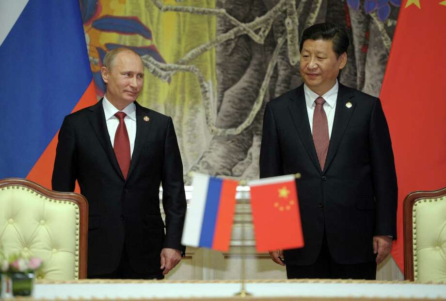 In this May 21, 2014, photo, Russia's President Vladimir Putin, and China's President Xi Jinping, right, smile during signing ceremony in Shanghai, China. China signed a long-awaited, 30-year deal Wednesday to buy Russian natural gas worth some $400 billion in a financial and diplomatic boost to diplomatically isolated President Vladimir Putin. The Obama administration is playing down an increasingly warm relationship between its main global rivals, China and Russia, that it may have inadvertently encouraged.  (AP Photo/RIA Novosti, Alexei Druzhinin, Presidential Press Service) Photo: Alexei Druzhinin, POOL / RIA Novosti Kremlin