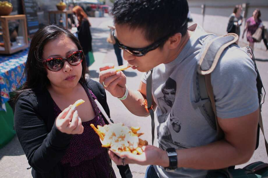 Tiffanie Cardenas and Richard Wong of San Jose dig in to some garlic crab fries at the 2014 Bottlerock Napa Valley music, food and wine festival on Friday, May 30, 2014 in Napa, Calif. Photo: Kevin N. Hume, The Chronicle