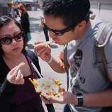 Tiffanie Cardenas and Richard Wong of San Jose dig in to some garlic crab fries at the 2014 Bottlerock Napa Valley music, food and wine festival on Friday, May 30, 2014 in Napa, Calif.