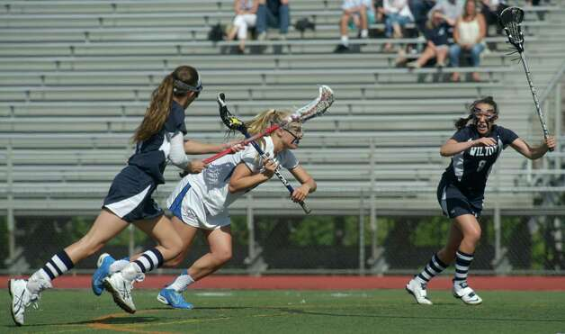 Darien's Hollis Perticone, #29, goes between Wilton's Laine Parsons, #17, and Cecily Freilich, #8, during the FCIAC girls lacrosse championship game between Wilton and Darien high school's, played at Brien McMahon High School, in Norwalk, Conn, on Friday, May 30, 2014. Darien is the FCIAC Girls Lacrosse Champion for 2014, beating Wilton 9-7. Photo: H John Voorhees III / The News-Times Freelance
