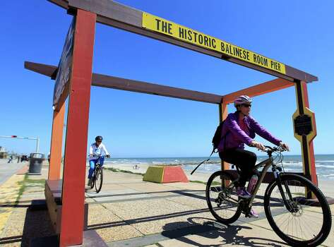 March 18, 2014: Bike riders go under the site of the historic Balinese Room pier on the Seawall in Galveston. Photo: Karen Warren, Staff / © 2014 Houston Chronicle