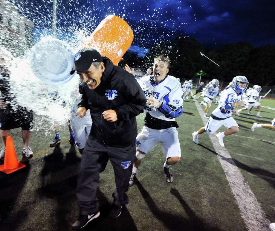 Darien boys lacrosse coach Jeff Brameier, left, gets the Gatorade bath from his player, Peter Lindley, right, after Darien won the FCIAC boys championship lacrosse match against Greenwich High School, 11-6, at Brien McMahon High School in Norwalk, Friday night, May 30, 2014. Photo: Bob Luckey / Greenwich Time