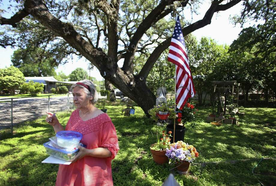 Carolyn Leslie brings food to a neighbor in their Whispering Oaks mobile home subdivision in Boerne. Photo: Photos By Timothy Tai / San Antonio Express-News / © 2014 San Antonio Express-News