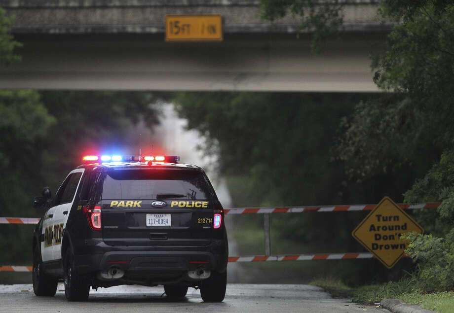 A park police officer guards the entrance to Olmos basin after rainfall last month. (File photo) Photo: John Davenport / San Antonio Express-News / ©San Antonio Express-News/John Davenport