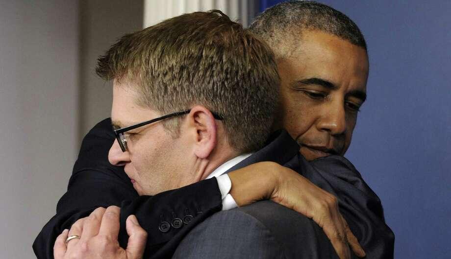 President Barack Obama hugs Jay Carney after announcing the press secretary's resignation. Photo: Associated Press / AP