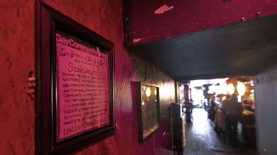 A framed copy of the Gay Community News hangs in the back room of the Stonewall Inn in New York's Greenwich Village, site of the famed gay-rights riots in 1969. Photo: Richard Drew / Associated Press / AP