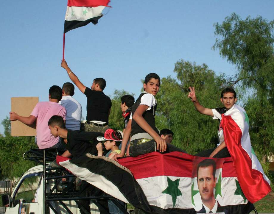 People rally on top of a car during a convoy rolling through Damascus, Syria, to encourage people to vote for President Bashar Assad in the June 3 election. Photo: Jonathan S. Landay / McClatchy-Tribune News Service / MCT