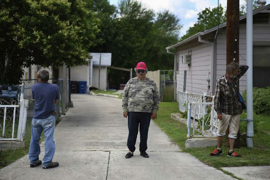 House manager Matt, who declined to give his last name (from left), and residents Frank Lucero and James Teague stand in the driveway of a boarding home on Pasadena Street. Photo: Photos By Timothy Tai / San Antonio Express-News / © 2014 San Antonio Express-News