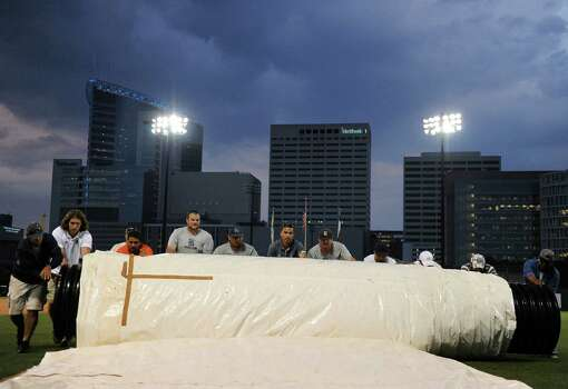 Field volunteers roll up a field tarp after a 1.5 hour weather delay before the start of a Houston NCAA baseball regional game between the Rice Owls and the George Mason Patriots, Friday, May 30, 2014, at Reckling Park in Houston. Photo: Eric Christian Smith, For The Chronicle