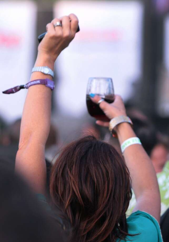 A woman holds her phone and wine over her head as she moves through the crowd at the 2014 Bottlerock Napa Valley music, food and wine festival on Friday, May 30, 2014 in Napa, Calif. Photo: Kevin N. Hume, The Chronicle