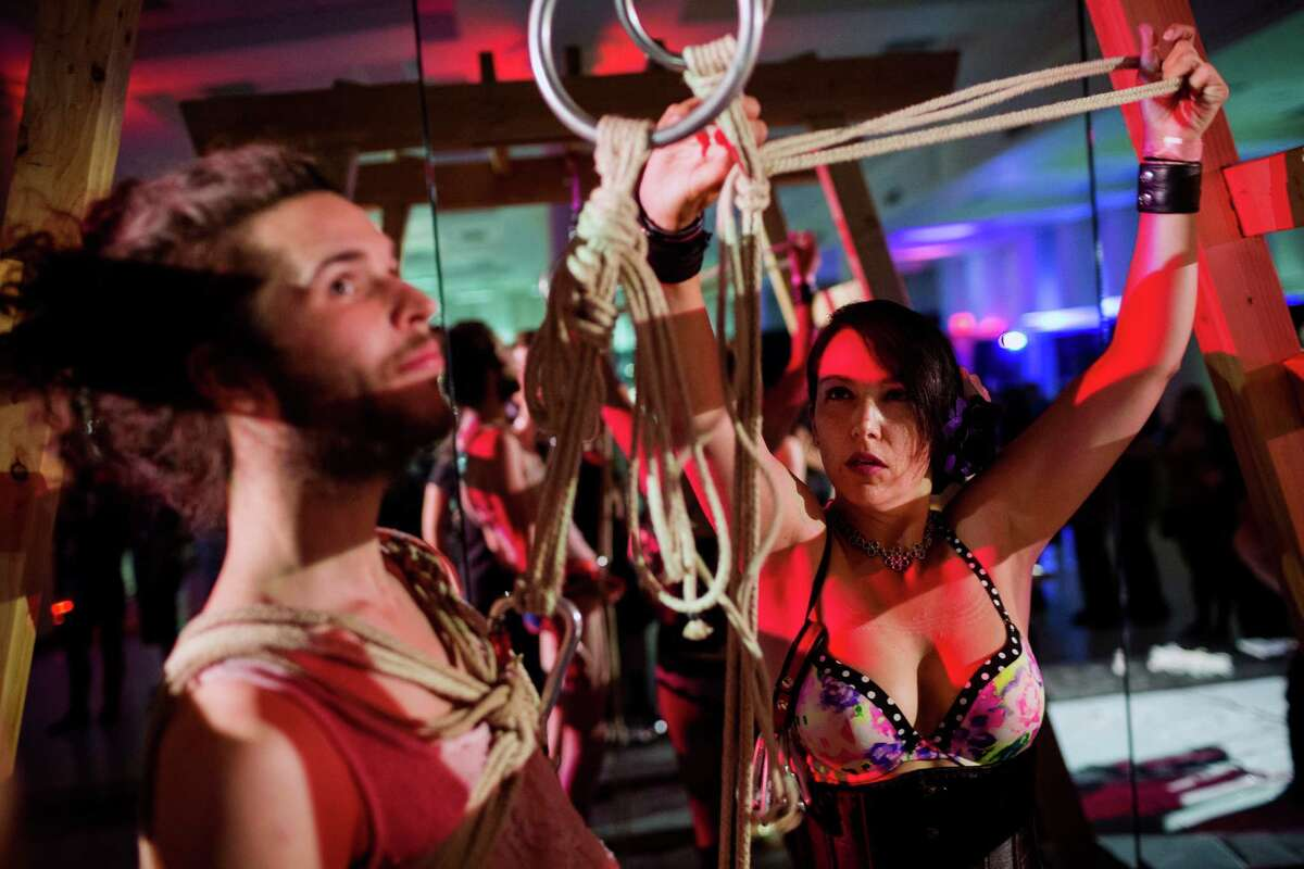 Bas Frost, 23, left, prepares to be suspended by ropes for the first time at the 12th annual Seattle Erotic Art Festival on Friday, May 30, 2014, in Seattle. The event, which continues through Sunday, aims to promote freedom of expression and foster a sex-positive culture through public celebration of the arts.
