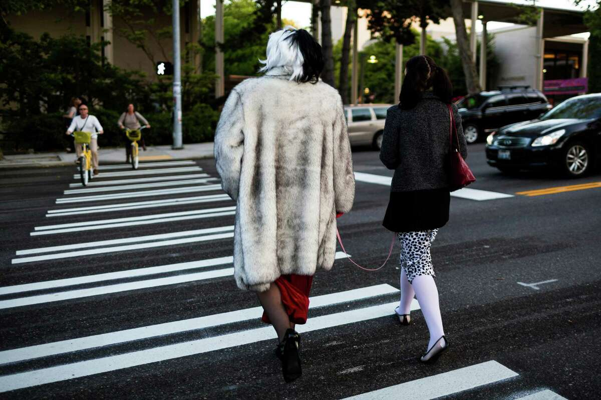 A couple dressed as Cruella de Vil and a leashed Dalmatian walk toward the entrance to the 12th annual Seattle Erotic Art Festival Friday, May 30, 2014, in Seattle.