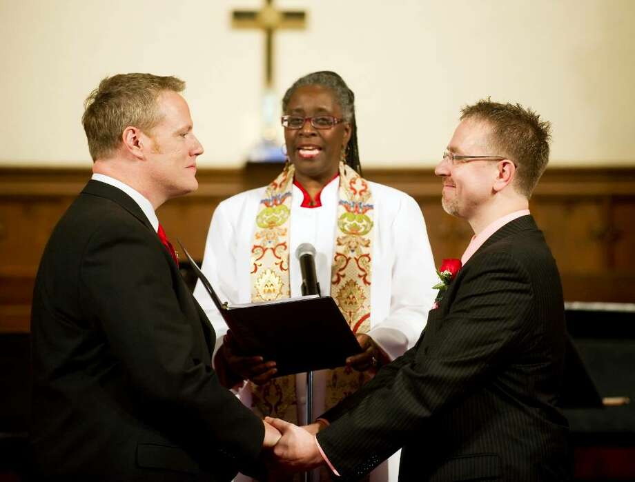 Joseph Belisle, left, and David Vintinner, right, exchange vows during their wedding ceremony conducted by the Rev. Cari Jackson, center, at the First Congregational Church in Stamford, Conn. on Sunday, Feb. 14, 2010. This was the first same-sex marriage performed at the church, the oldest in Stamford. Photo: Chris Preovolos / Stamford Advocate