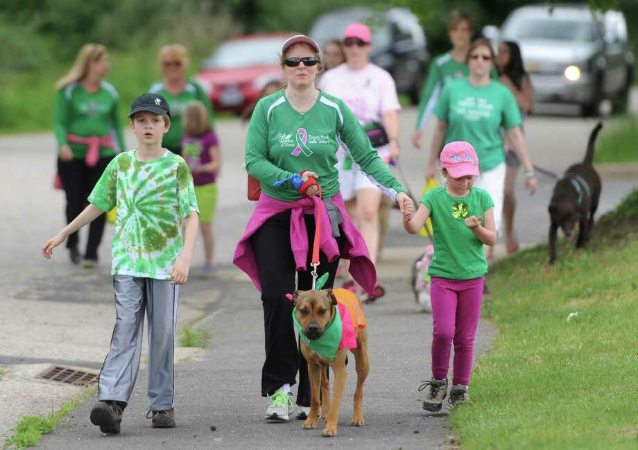 Aimee Tabor, of Sandy Hook, walks her dog, Wiley, a boxer-lab mix, with her children Kyle, 8, and Nichole, 6, at the Strut Your Mutt dog walk at the Park and Bark dog park in Newtown, Conn. Saturday, May 31, 2014.  The event, now in its fifth year, took place for the at the new dog park behind Reed Intermediate School that opened on May 3.  Th event featured vendors, a canine agility course, hot dog toss, and the Strut Your Mutt pageant. Photo: Tyler Sizemore / The News-Times