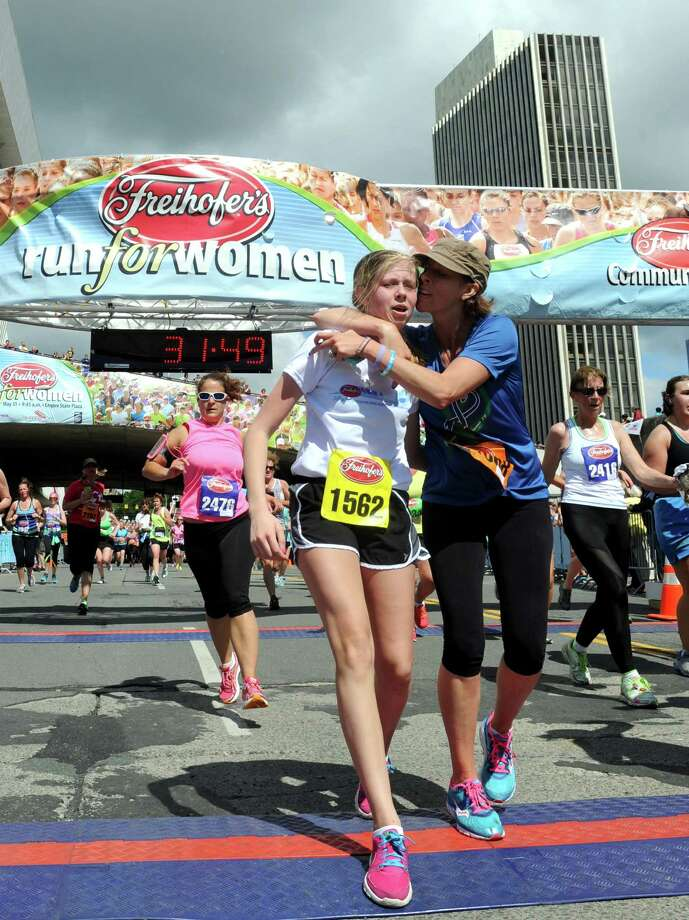 Lori Mungel, right, of Clifton Park gives her soon to be 14-year-old daughter Makenna Mungel, she turns 14 on 6/1/2014, a kiss as they cross the finish line during the Freihofer's 36th  Run for Women on Saturday May 31, 2014 in Albany, N.Y. (Michael P. Farrell/Times Union) Photo: Michael P. Farrell / 00027076A