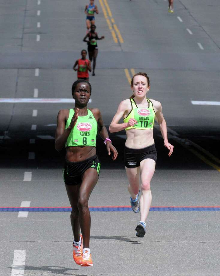 Elite runners Agnes Cheserek of Kenya, left, and Megan Hogan of Saratoga battle to the finish during the Freihofer's 36th  Run for Women on Saturday May 31, 2014 in Albany, N.Y. (Michael P. Farrell/Times Union) Photo: Michael P. Farrell / 00027076A
