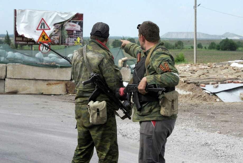 Pro-Russian armed militants point at Slavyansk, Ukraine. Photo: VIKTOR DRACHEV, Staff / AFP