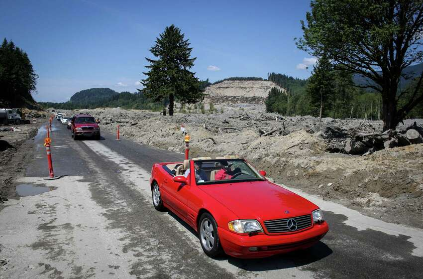 Some of the first cars to drive on a newly reopened state Route 530 make their way along the road.
