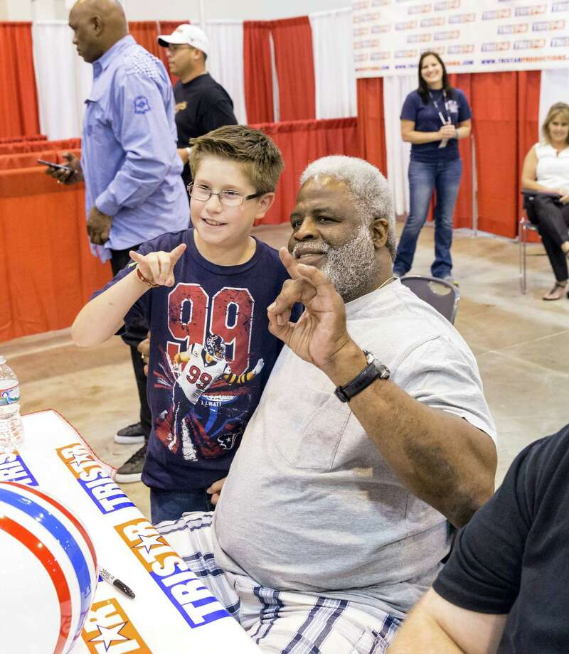 """The Tristar 28th Annual Summer Collectors Show is being held this weekend at NRG (Reliant) Center, Hall E. Thousands attend to buy and sell memorabilia and get autographs and photographs with sports stars. ID: Earl Campbell poses with 9-year-old Jordan Escobedo as they flash the """"Hook 'em Horns"""" sign. Saturday  May 31, 2014 Photo: Craig Hartley, For The Chronicle / Copyright: Craig H. Hartley"""