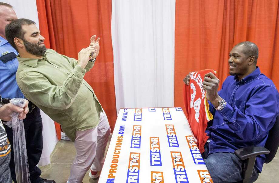 The Tristar 28th Annual Summer Collectors Show is being held this weekend at NRG (Reliant) Center, Hall E. Thousands attend to buy and sell memorabilia and get autographs and photographs with sports stars. ID: Ibrahim Arch captures the moment as Hakeem Olajuwon holds up a freshly-signed jersey.  Saturday  May 31, 2014 Photo: Craig Hartley, For The Chronicle / Copyright: Craig H. Hartley