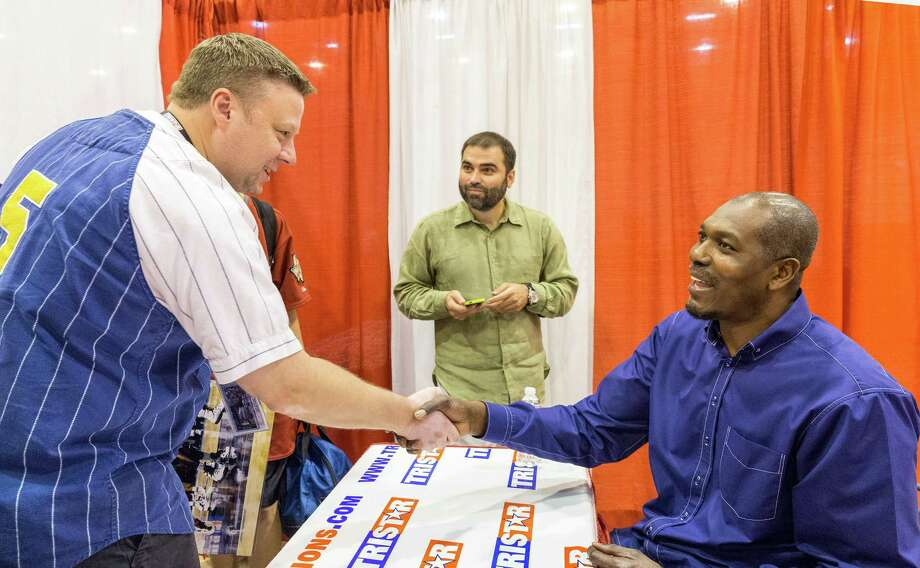 The Tristar 28th Annual Summer Collectors Show is being held this weekend at NRG (Reliant) Center, Hall E. Thousands attend to buy and sell memorabilia and get autographs and photographs with sports stars. ID: Tony Bacewicz of Dallas is delighted to shake hands with Hakeem Olajuwon. In center is Ibrahim Arch. Saturday  May 31, 2014 Photo: Craig Hartley, For The Chronicle / Copyright: Craig H. Hartley