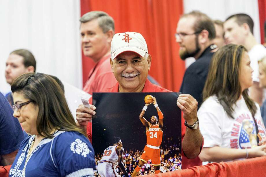The Tristar 28th Annual Summer Collectors Show is being held this weekend at NRG (Reliant) Center, Hall E. Thousands attend to buy and sell memorabilia and get autographs and photographs with sports stars. ID: Ralph Sifuentes holds up a poster as he waits in line to get an autograph by Hakeem Olajuwon. Saturday  May 31, 2014 Photo: Craig Hartley, For The Chronicle / Copyright: Craig H. Hartley