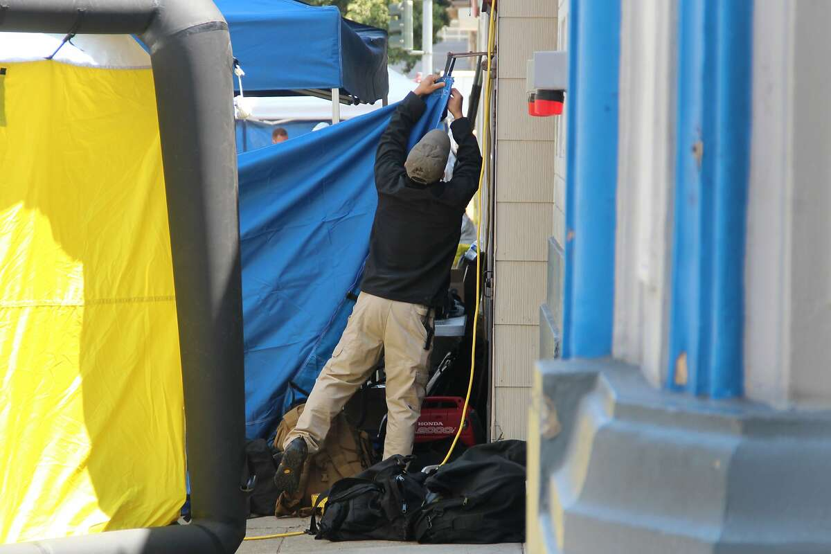A law enforcement agent hangs a curtain to obstruct the view of the public and the press while FBI agents serve a warrant at a building on Jackson Street near Polk on May 31, 2014 in San Francisco, Calif.