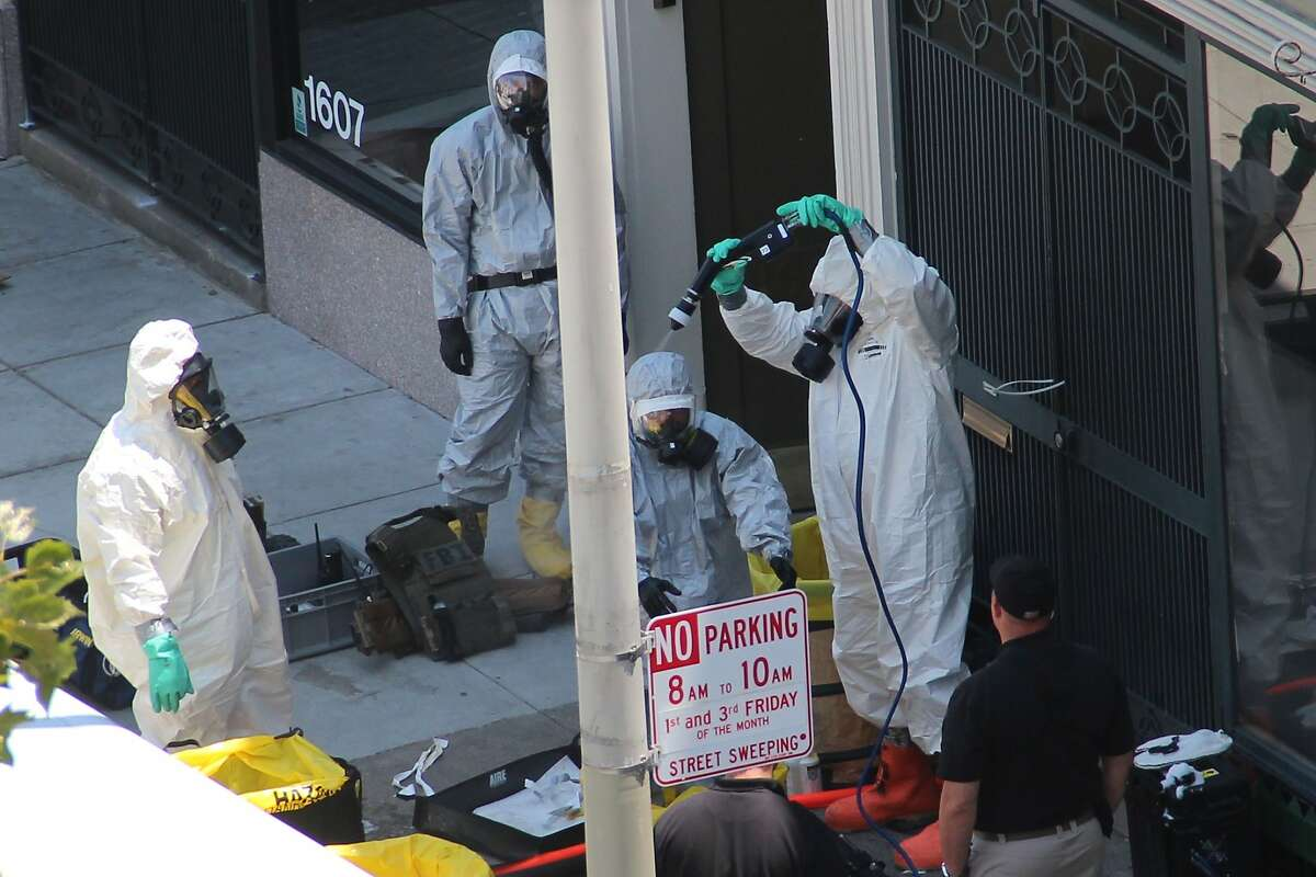 Law enforcement agents in HAZMAT suits spray down an agent that just exited a building on Jackson Street near Polk where the FBI was serving a warrant on May 31, 2014 in San Francisco, Calif.
