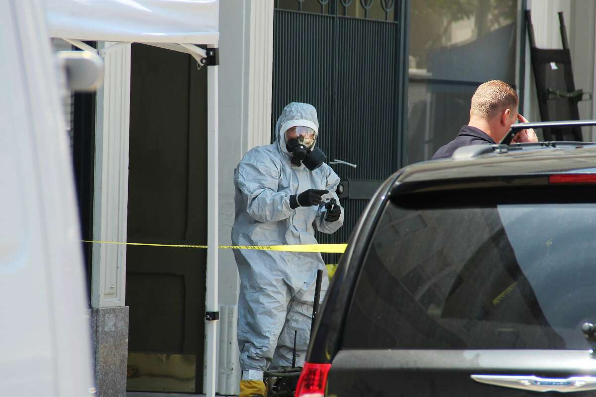 A person wearing a HAZMAT suit gestures after leaving a building on Jackson Street near Polk where FBI agents served a warrant on May 31, 2014 in San Francisco, Calif.