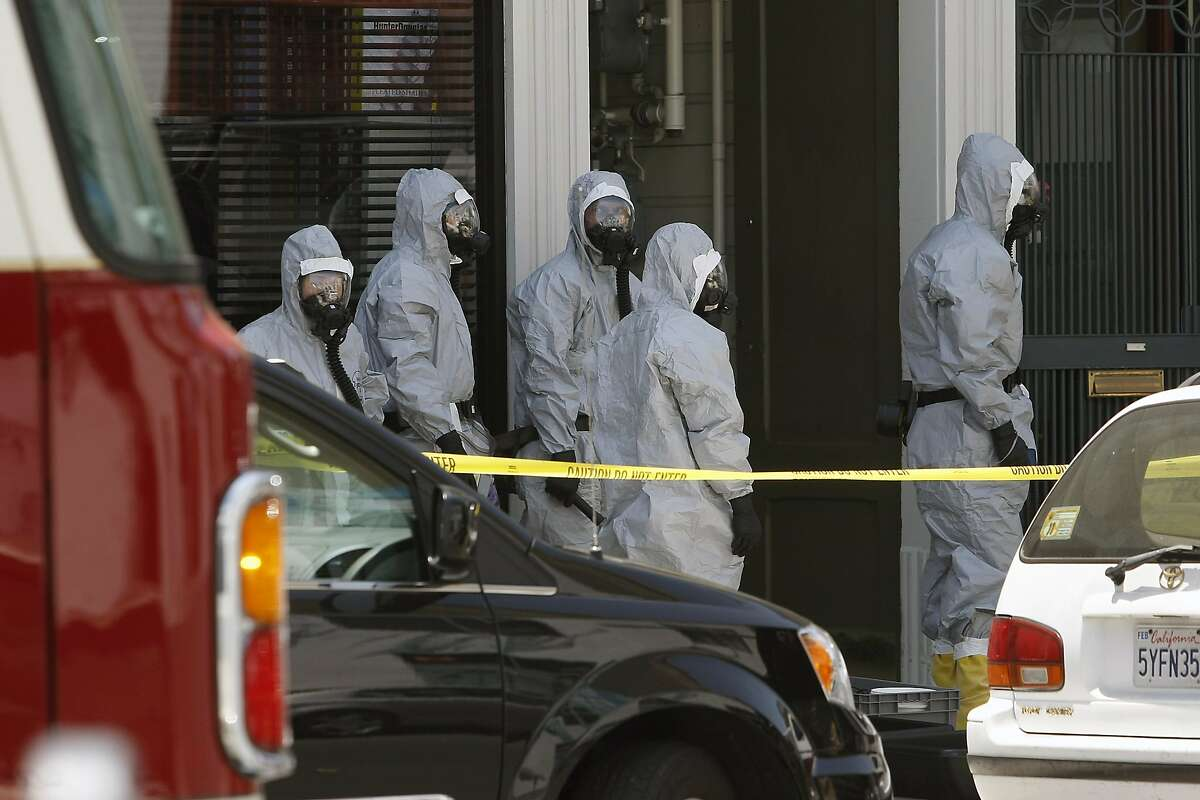 Agents in haz-mat suits are seen as the FBI searches a building on Jackson St. between Polk and Van Ness in San Francisco, CA, Saturday May 31, 2014.