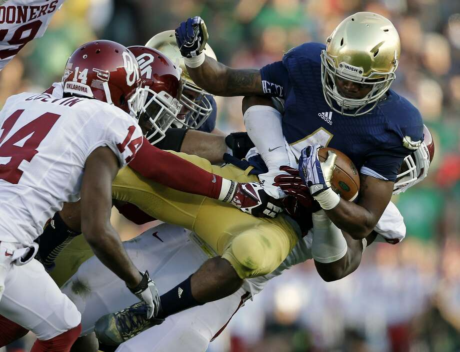 Notre Dame's George Atkinson III, shown being tackled by Oklahoma players, signed with the Raiders as a free agent. Photo: Darron Cummings, Associated Press